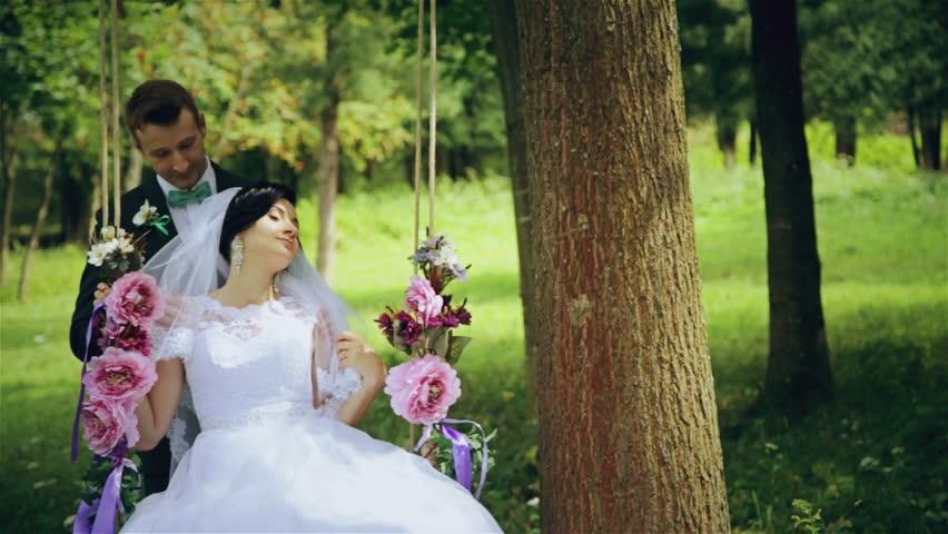 Lovely Wedding Couple Swing Of Flowers In The Garden