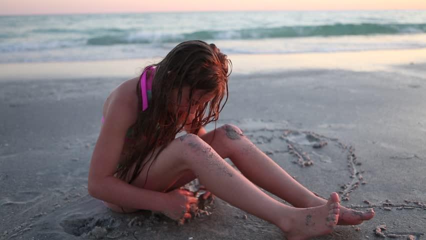 Pre-teen girl playing on beach at sunset   Shutterstock HD Video #13561100