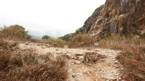 Deserted open former quarrying area, steep rocky mountain wall, dry grass and sandy pathway. POV camera move forward on track, walkway path on dry ground