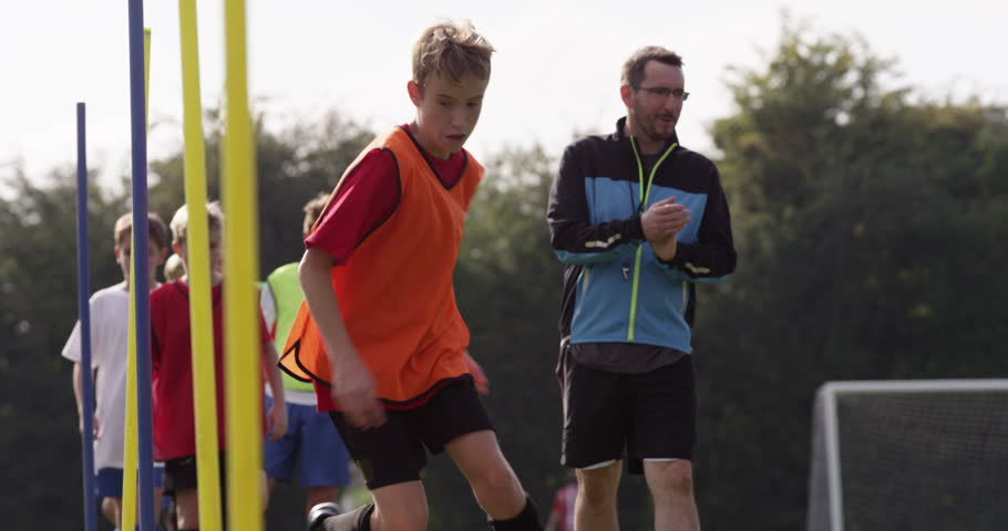 Football coach praising a boy during the training.