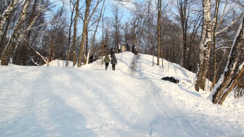 Boy slid down slope and rolled over, several people stand on hill at sunny winter day