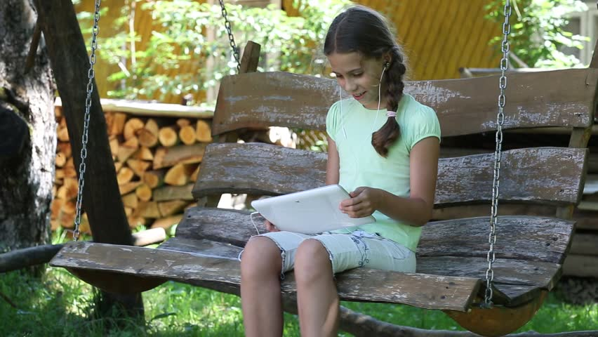 Superb Video Bench Part - 12: Pretty Girl With Tablet Computer Sits On The Swing Bench. Girl Playing The  Game On