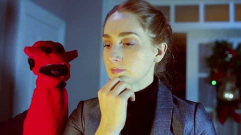 Conscience concept, devil puppet talking to woman