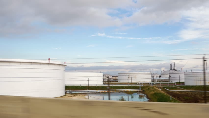 Slow motion driving along highway next to a storage tanks of a the petrochemical processing plant. | Shutterstock HD Video #13662572