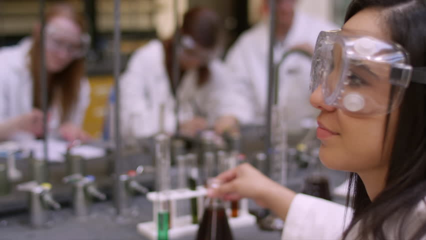 Students in a science lab observing a liquid in their beakers | Shutterstock HD Video #13667012
