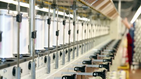 Textile Industry. Row of automated machines for yarn manufacturing. 