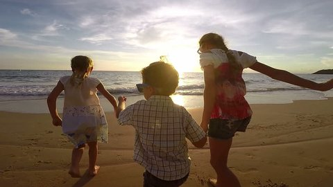 Happy children playing on the beach at the sunset time. Concept of happy friendly family.