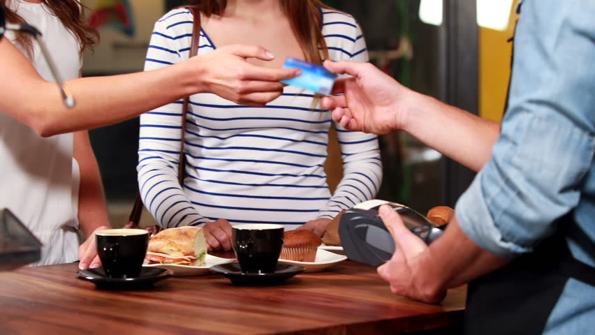 Smiling customer typing her code on credit card reader in a cafe