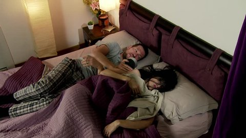 Man trying to wake up wife in bed in the morning