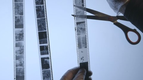 Photographer inspects strips of 35mm black and white film negatives in dark room before cutting and archiving