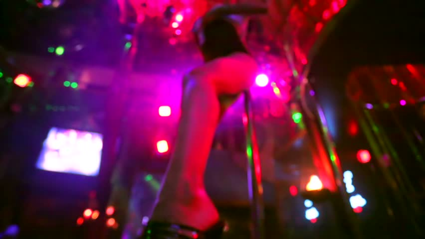 Defocused view, sexy woman dancing on a stage in a strip club.
