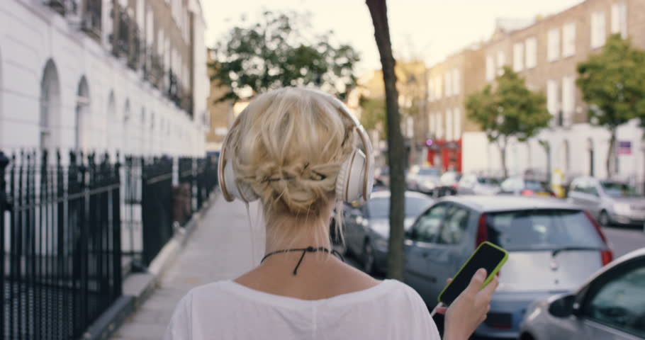 Happy Beautiful blonde listening to music on smart phone walking in the city | Shutterstock HD Video #13831964
