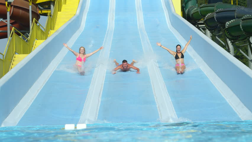 SLOW MOTION: Young adults sliding down extreme water slide toboggan screaming and smiling in hot summer on vacation