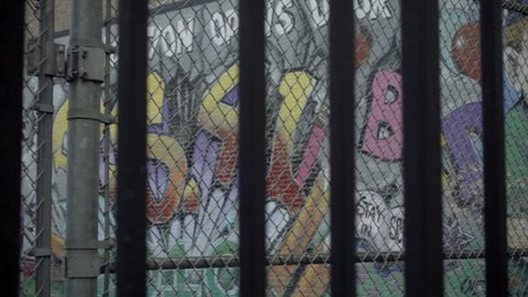 NEW YORK - DEC 16, 2015: graffiti on public school yard wall, fence and gate panning to parked Citi Bikes lined up docking station and old man walking NYC. P.S. 41 has a fence on Greenwich Avenue.