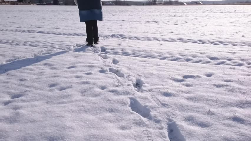 Woman walking on snowy path. Weight loss concept. Lifestyle footage from winter season.
