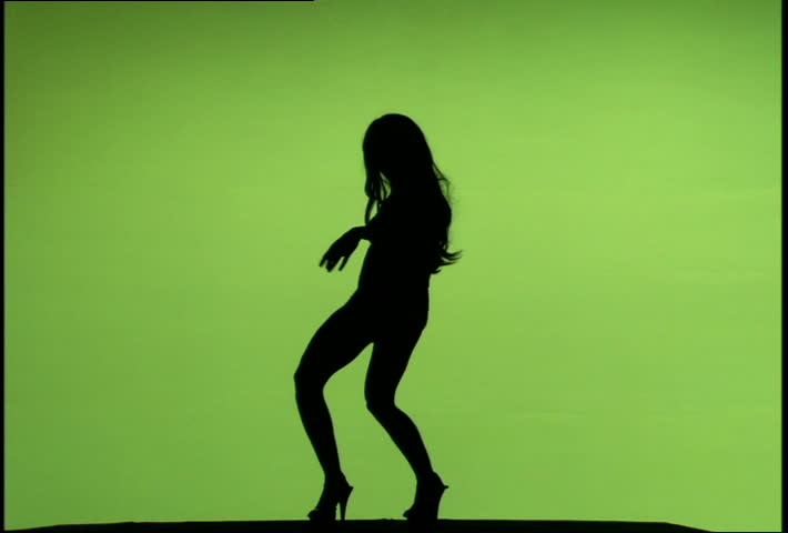 A silhouette of a woman dancing against a green screen background