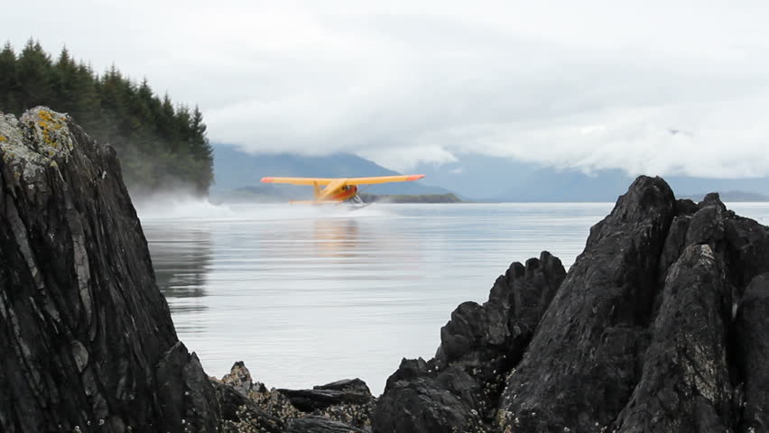 Seaplane, framed by beautiful, craggy boulders, glides on rippling water as it prepares to takeoff into thick clouds hanging over mountains.