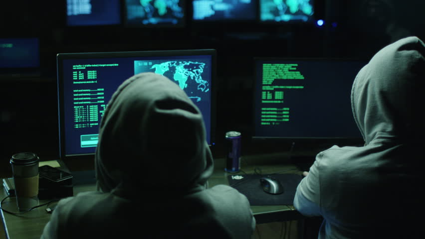 Two hackers in hoods work on a computers with maps and data on display screens in a dark office room. Shot on RED Cinema Camera in 4K (UHD).
