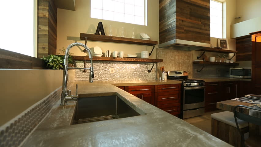 Modern Kitchen Dolly Right and Sun Flare Through Window. camera moves right on a modern kitchen. Sun flare coming through large windows showing all details of the kitchen and from the sink