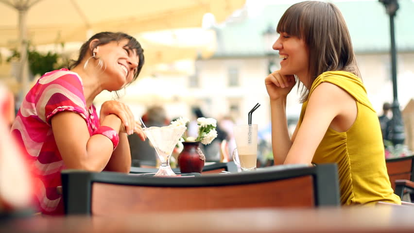 Female friends meeting after shopping in restaurant, outdoors, camera stabilizer shot