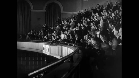 Side view of audience in balcony fervently applauding, 1940s