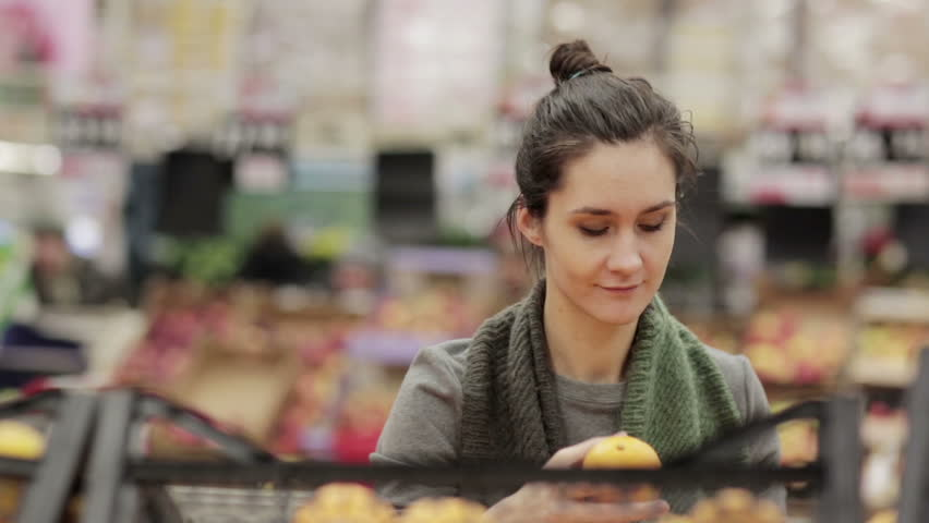 Young woman chooses ripe oranges on store shelves. | Shutterstock HD Video #14035832