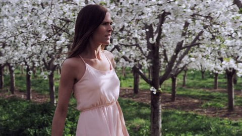girl playfully walks through white blossoms in orchard