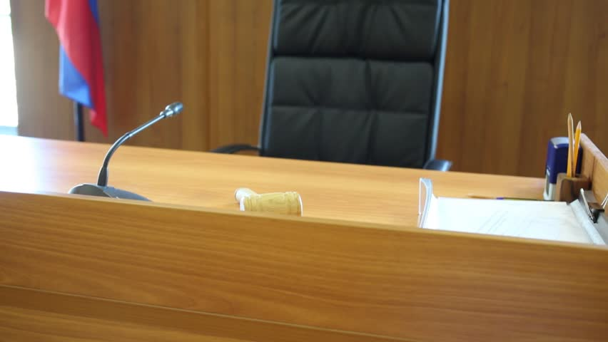 Judgment seat with hammer in empty light courtroom