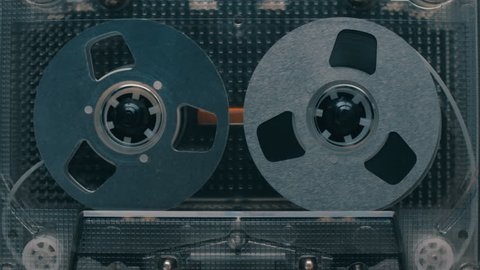 Cassette with chrome color reels in the tape deck recorder is rapidly rewound. Time-lapse. Closeup