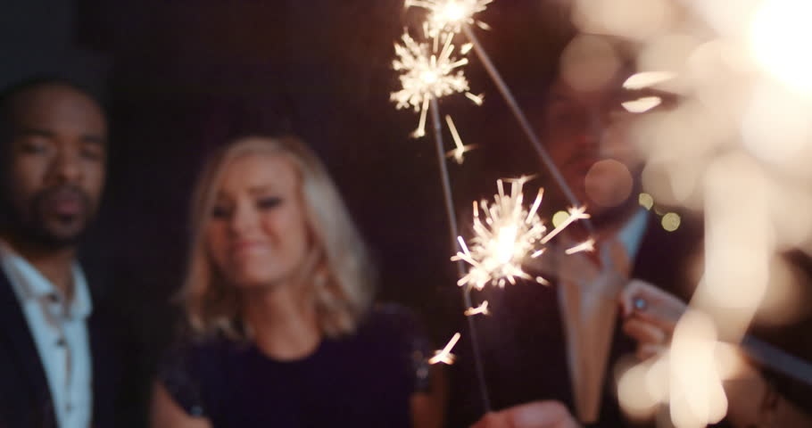 Sexy happy group of friends at glamorous party lighting sparklers having fun smiling celebrating new year's eve.   Shutterstock HD Video #14075972