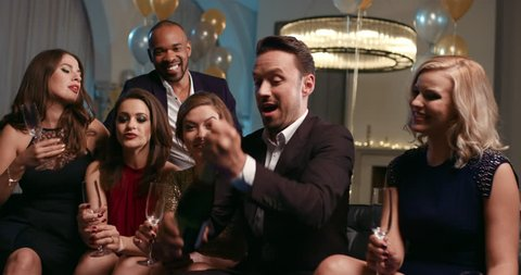 Friends holding up champagne flutes together in a toast at sexy glamorous party celebration cheers
