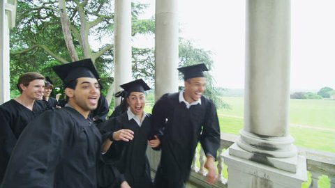 Happy and excited mixed ethnicity group of student friends on graduation day running along outside their university building. In slow motion.