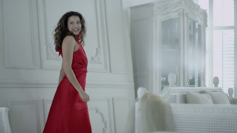 4k / Ultra HD version Happy and beautiful brunette in red evening gown runs to look out of the window in her elegant white apartment. In slow motion. Shot on RED Epic