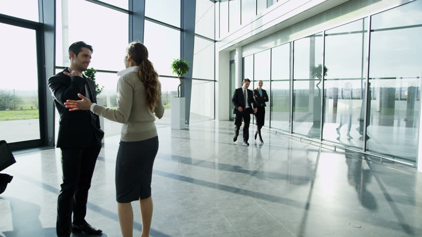 4k / Ultra HD version An attractive businessman and businesswoman are having a conversation in a bright modern office building. Others workers in the building walk past them. Shot on RED Epic | Shutterstock HD Video #14126951