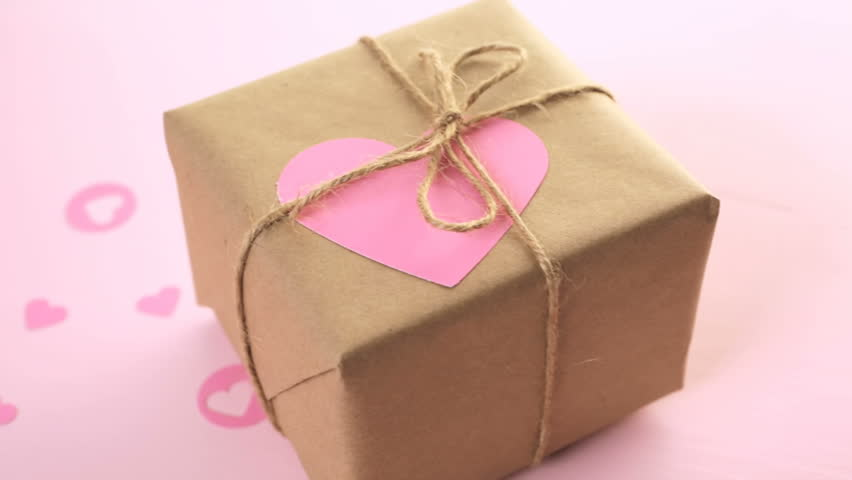 Gift box wrapped in recycled paper and decorated with pink heart gift box wrapped in recycled paper and decorated with pink heart hd stock footage negle Images
