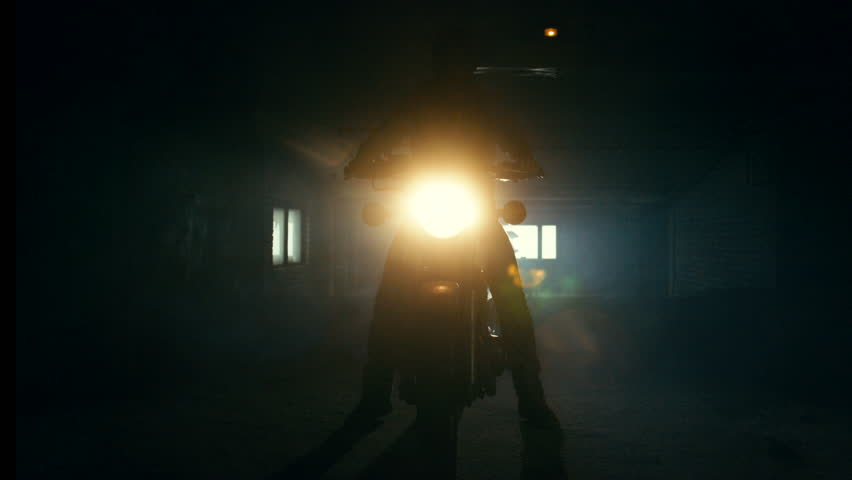 Silhouette of young male biker turning on a headlight of his motorbike at night. 