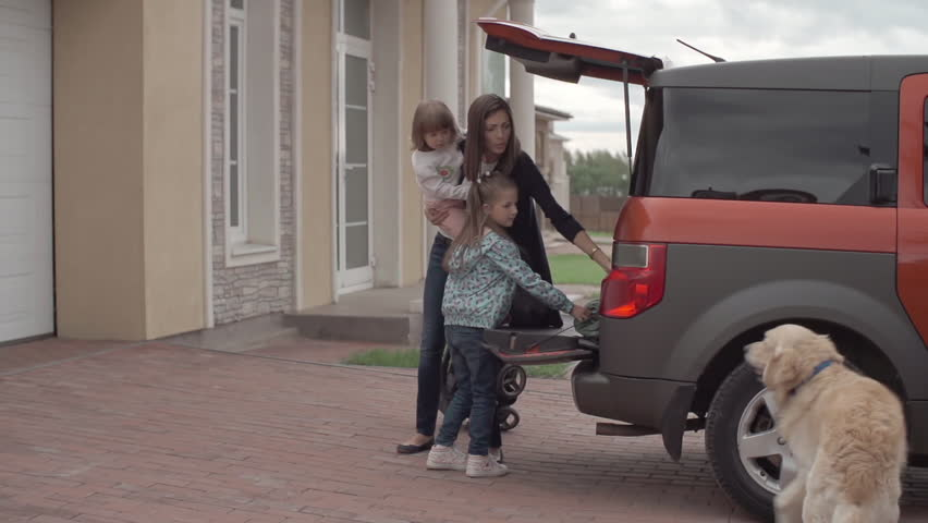 Mom and her little daughters taking their stuff from trunk of the car while their cute lab walking around them