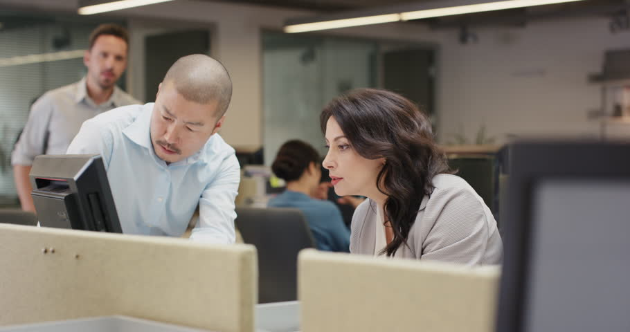 Woman manager leading diverse team meeting in small business. Three people working around computer late at night | Shutterstock HD Video #14142230