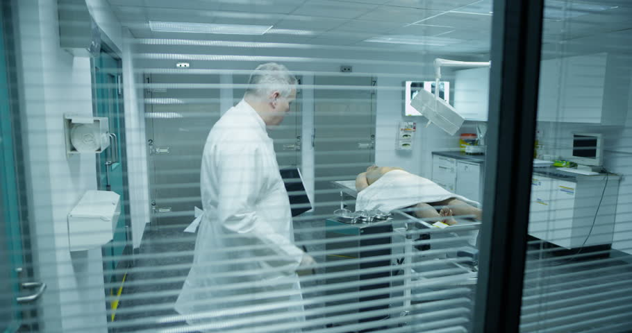 4k / Ultra HD version The lifeless naked corpse of a young mixed race male is laid out on the autopsy table, ready for the medical examiner. He checks the toe tag and starts to make notes. Slow motion