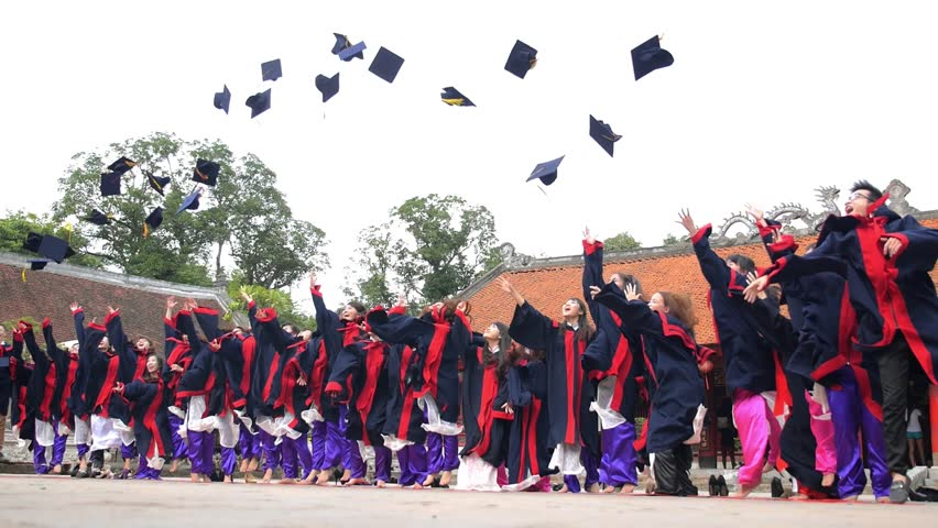 HANOI, VIETNAM - JUL 7, 2015. Cheerful Students Throwing Graduation Caps in the Air