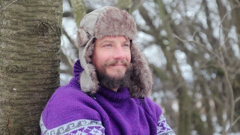 Portrait of a young handsome man with a beard. A bearded man in the winter woods. Healthy young bearded man in nature.