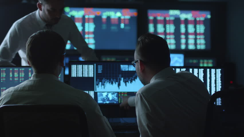 Team of stockbrokers are having a conversation in a dark office with display screens. Shot on RED Cinema Camera in 4K (UHD). | Shutterstock HD Video #14161592