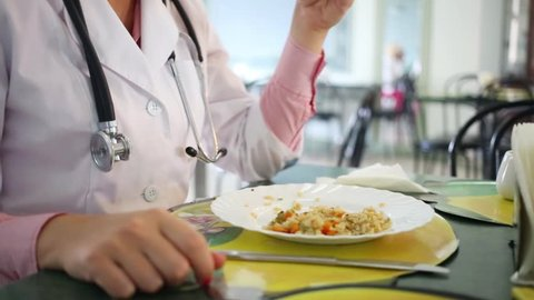 Doctor with stethoscope around her neck dines in a hospital canteen
