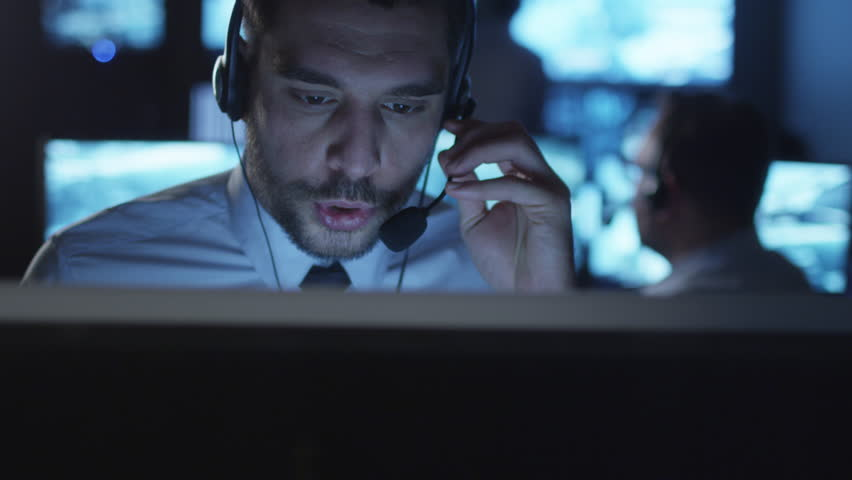 Happy technical support specialist is drinking coffee while working on a computer in a dark monitoring room filled with display screens. Shot on RED Cinema Camera in 4K (UHD). | Shutterstock HD Video #14186648