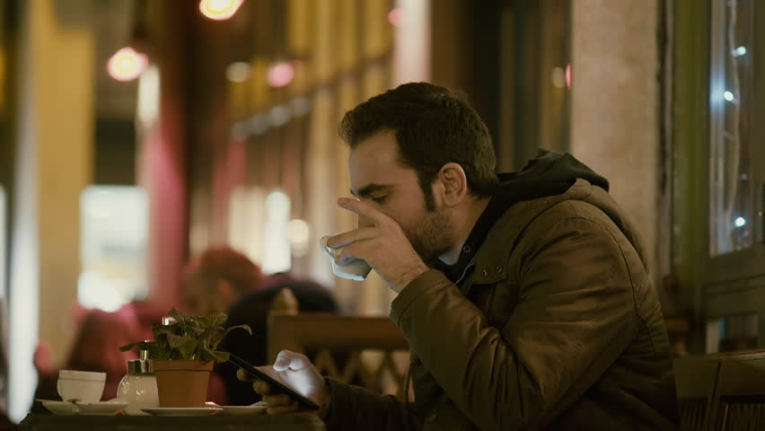 Young man sitting in night cafe/bistro browsing with tablet with a happy/laughing face, outside at winter at night after work drinking coffee and browsing his sites and social media on his tablet. | Shutterstock HD Video #14190692