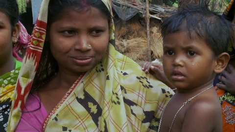 Baruipur, India - CIRCA 2013 - Mother in the jungle with child in arms smiles and looks at camera