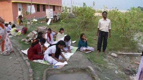 Baruipur, India - CIRCA 2013 - Girls doing school assignment on blankets