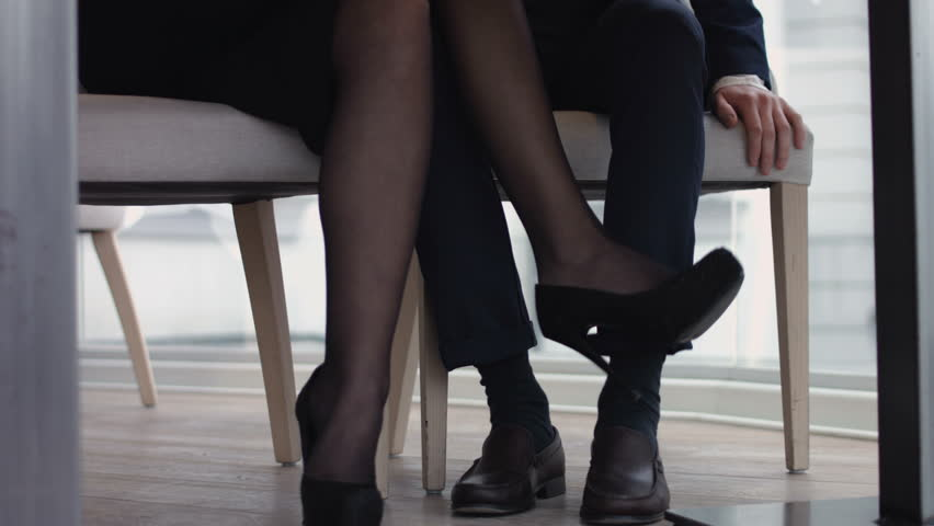 Young Flirting With Legs At The Restaurant Under Table