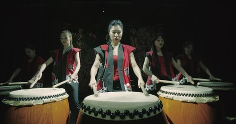 a group of Japanese Taiko drummers girls , start playing with the jump dark background, slow motion