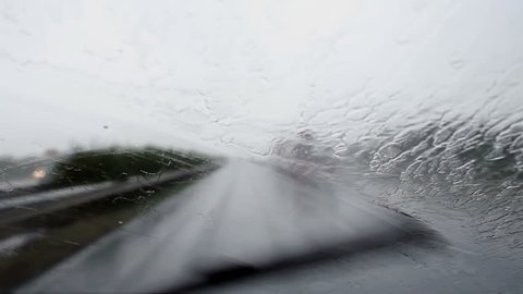 Car wipers removing heavy rain from the windshield during ride